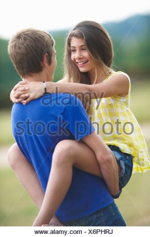 Teenage couple hugging outdoors - Stock Photo