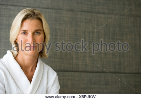 Portrait of smiling woman in white bathrobe - Stock Photo