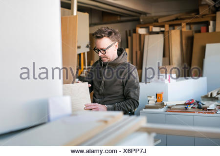 Carpenter with wood planks in workshop - Stock Photo