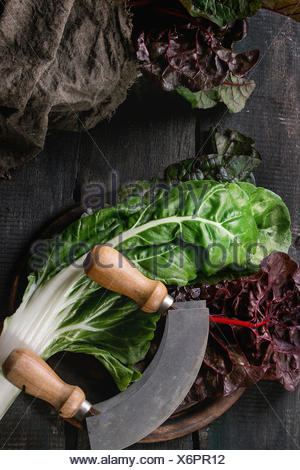 Variety of fresh chard mangold salad leaves on woode chopping board with vintage knife and sackcloth rag over old dark wooden ba - Stock Photo