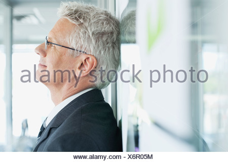Close-up of businessman leaning on wall in office - Stock Photo