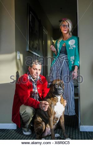 Couple in hallway with boxer dog looking at camera - Stock Photo