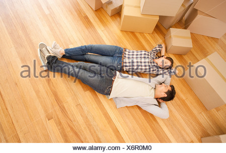Couple laying on floor of new house - Stock Photo