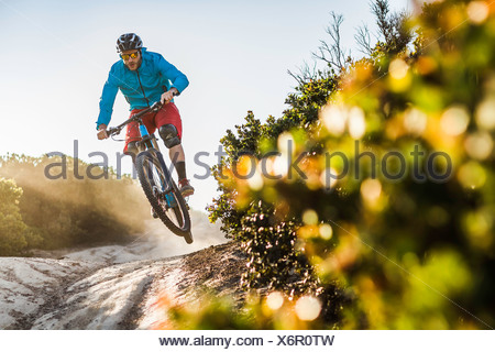 Young man mountain biking over rocks, Monterey, California, USA - Stock Photo