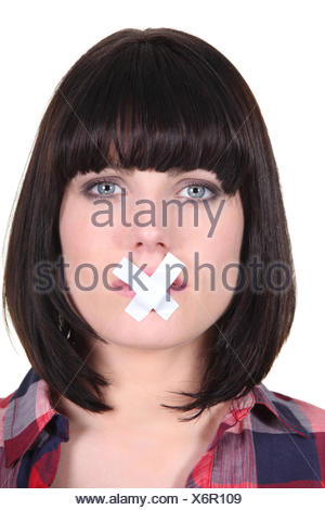 woman with a scotch tape on her mouth - Stock Photo