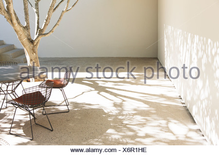 Table and chairs casting shadows in courtyard - Stock Photo