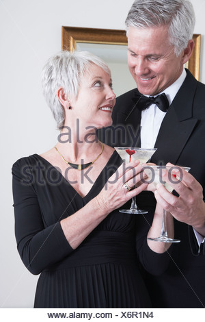 Smiling mature couple in evening wear holding cocktails - Stock Photo