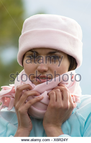 portrait attractive young woman posing outdoors wearing pink fleecy hat - Stock Photo