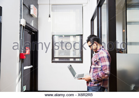Young man holding laptop in corridor - Stock Photo