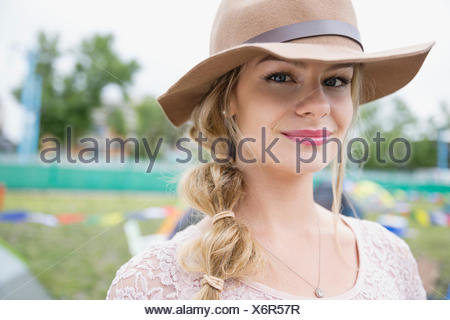Portrait smiling young blonde woman wearing hat - Stock Photo
