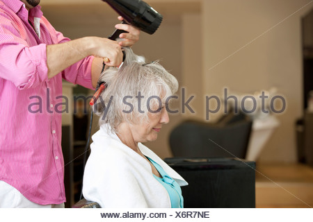 A senior woman having her blow dried at a hairdressing salon - Stock Photo