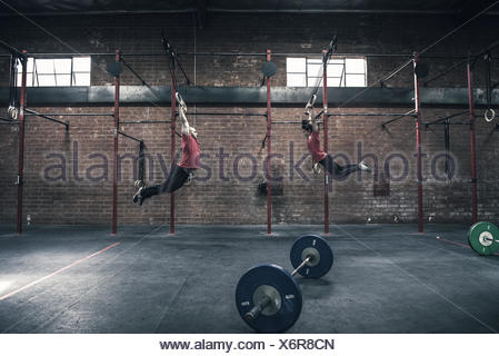 Young man and woman swinging on gym rings in gym - Stock Photo