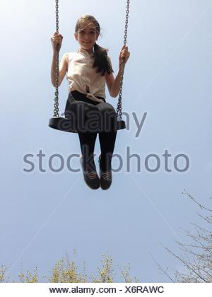 Girl sitting on a swing - Stock Photo