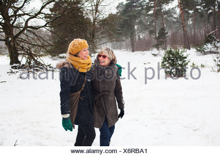 Mother and daughter walking in snow - Stock Photo