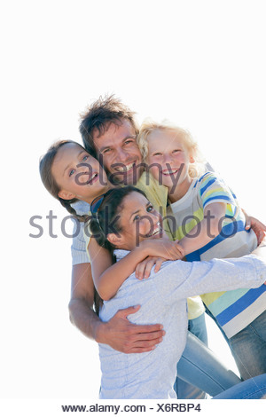 Portrait of enthusiastic family hugging - Stock Photo