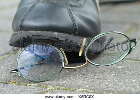 boy steps on eyeglasses - Stock Photo