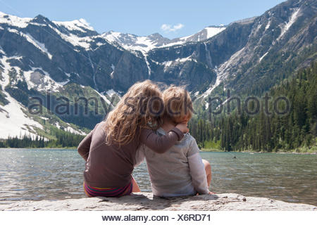 Young siblings enjoying view of mountains in Glacier National Park, Montana, USA - Stock Photo