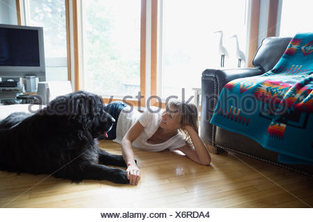 Woman and dog laying face to face floor - Stock Photo