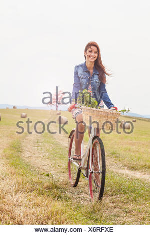 Teenager riding bicycle on field, Roznov, Czech Republic - Stock Photo