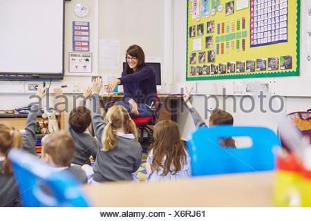 Teacher questioning children sitting on floor in elementary school classroom - Stock Photo