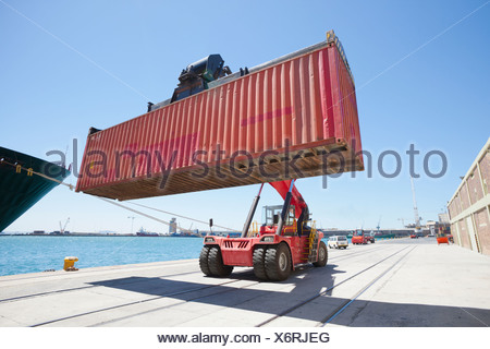 Mobile crane moving container ship at commercial dock - Stock Photo