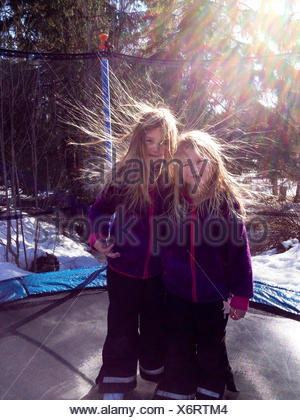 Two girls with static hair standing on a trampoline in the garden, Sweden - Stock Photo