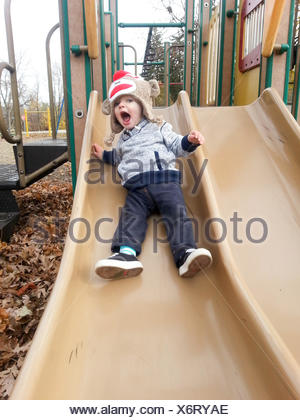 Boy sliding on playground - Stock Photo