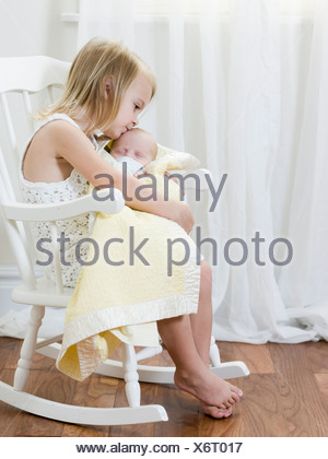 big sister holding her newborn brother - Stock Photo