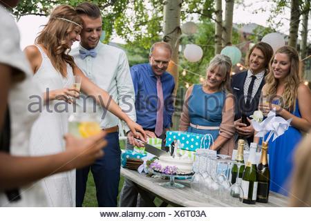 Bride and groom cutting cake backyard wedding reception - Stock Photo