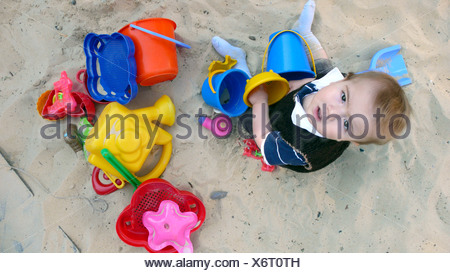 little boy playing in a sandpit - Stock Photo