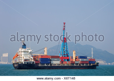 China, Hong Kong, Container Ship being Unloaded by Lighter - Stock Photo