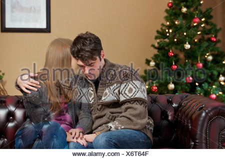 Man holding fading girlfriend?on sofa - Stock Photo