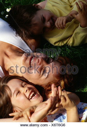 Mother laying on grass with children, view from above. - Stock Photo