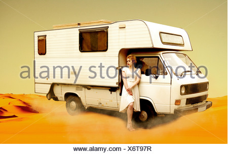 Germany, Berlin, Young woman standing next to camping bus in desert - Stock Photo