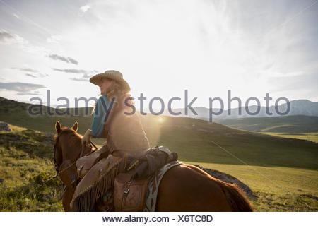 Female rancher horseback riding in remote sunny field - Stock Photo