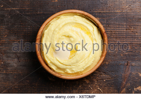 Mashed potatoes in wooden bowl on dark background - Stock Photo