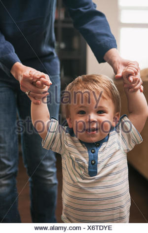Little boy learning to walk with help from mother - Stock Photo