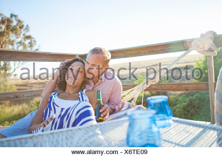 Young couple relaxing on hammock on balcony - Stock Photo