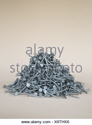 heaped pile of galvanized nails - Stock Photo