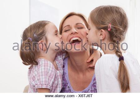 Germany, Munich, Girls (4-7) kissing on mother's cheek - Stock Photo