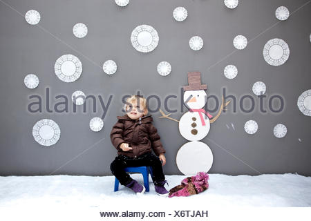Baby girl with snowflake and snowman cutouts - Stock Photo