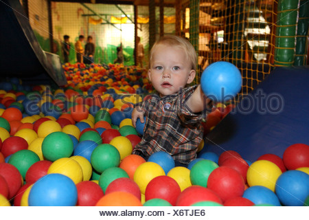 Indoor children's playground young child plays in a ball pool - Stock Photo