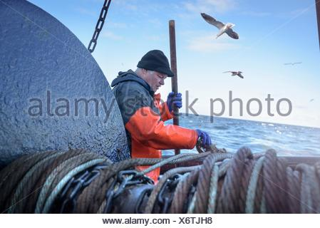 Fisherman preparing net on trawler - Stock Photo