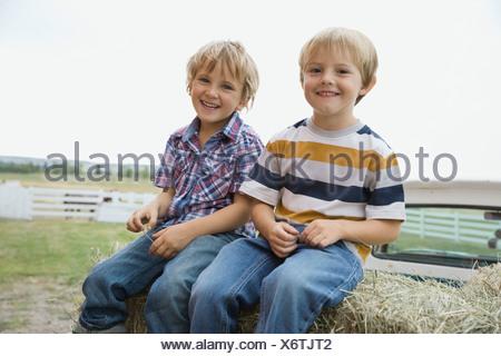 Portrait of happy couple sitting on hay bales - Stock Photo