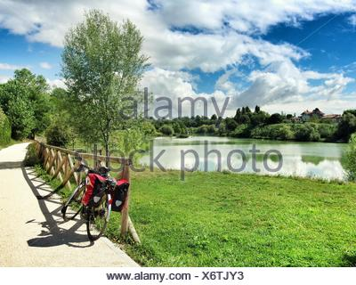 Bicycle Parked On Footpath By Lake Against Cloudy Sky - Stock Photo