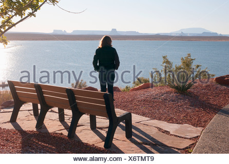 A Woman Stands By A Bench Looking Out Over Lake Powell; Arizona, United States of America - Stock Photo