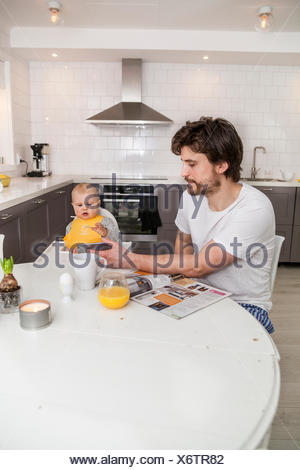 Sweden, Father and son (12-17 months) sitting in kitchen