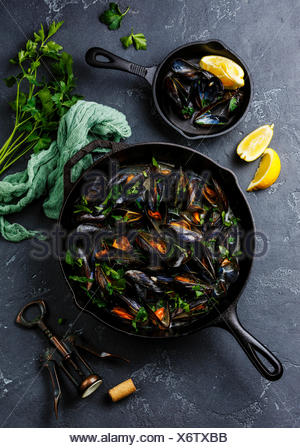 Mussels in black cooking pan with parsley on dark stone background