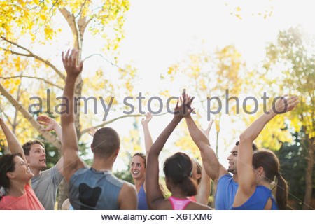 Fitness class giving each other a high five after class. - Stock Photo