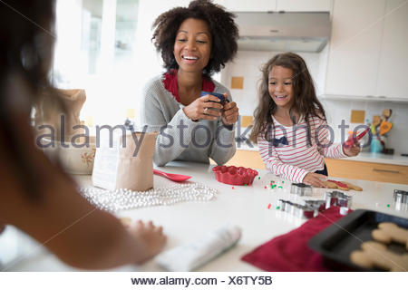 Mother and daughters decorating Christmas gingerbread cookies in kitchen - Stock Photo